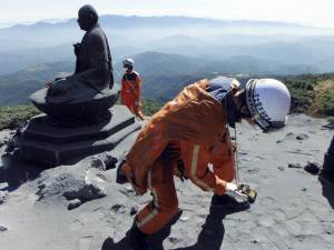 Scientist checking gas emissions next to a Buddha statue on Ontake